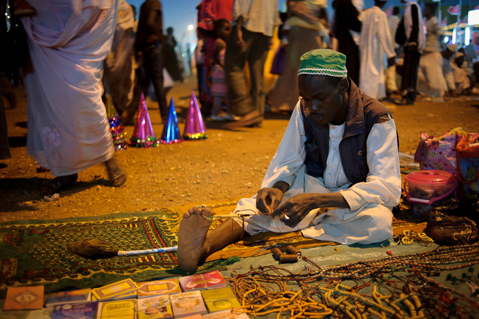 A Sudanese man threads Islamic prayer beads to sell during Mawlid celebrations.