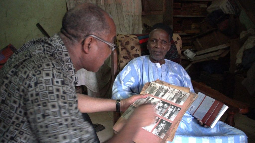 Cherif Keita viewing photo album with Malick Sidibé.